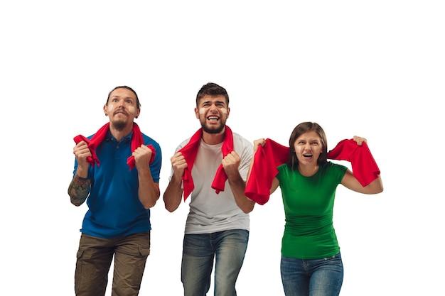 Razem. trzech fanów piłki nożnej kobiet i mężczyzn doping dla ulubionej drużyny sportowej z jasnymi emocjami na białym tle studio. wygląda na podekscytowanego, wspierającego. pojęcie sportu, zabawy, wsparcia.