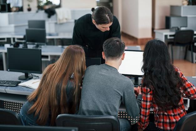 Razem w pobliżu jednego monitora. grupa młodych ludzi w ubranie pracujących w nowoczesnym biurze