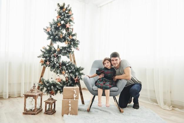Razem w pokoju. boże narodzenie i święta koncepcja. śliczna mała dziewczynka z ojcem siedzi na krześle obok drabiny ozdobionej gwiazdami i pudełkami na prezenty na podłodze.