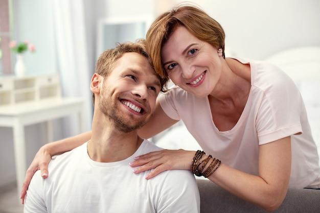 Razem z synem. miła pozytywna kobieta patrzy na ciebie, będąc razem ze swoim synem