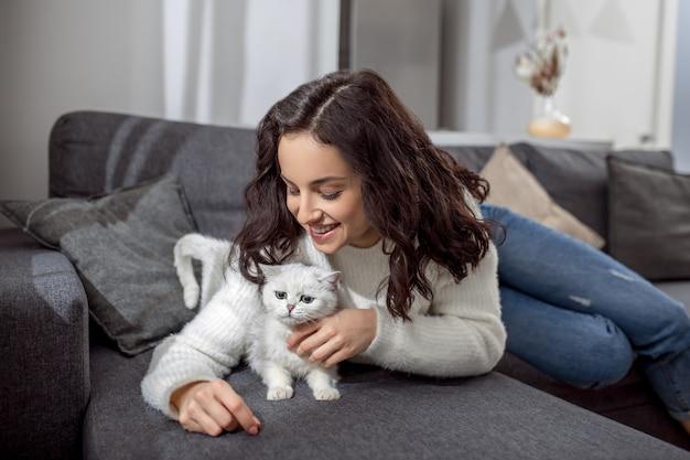 Razem ze zwierzakiem. śliczna młoda kobieta spędza weekend w domu i czuje się spokojna