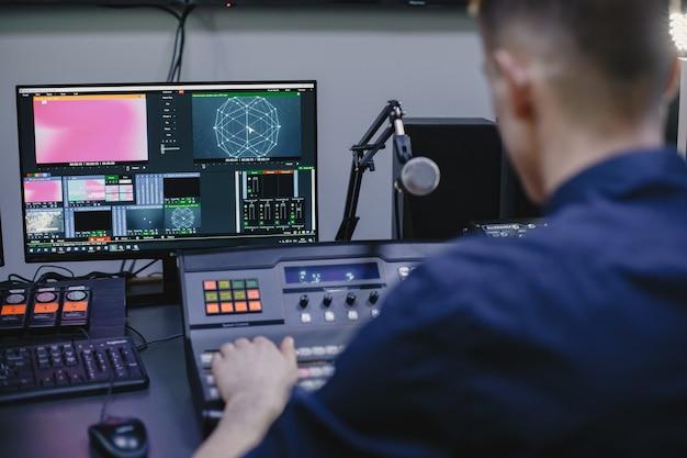 Realizator dźwięku pracujący w studio ze sprzętem