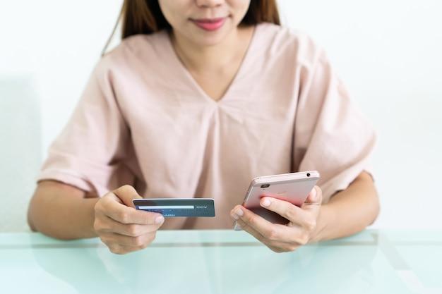Ręce azjatyckich kobiety za pomocą telefonu komórkowego, trzymając kartę kredytową w kawiarni.
