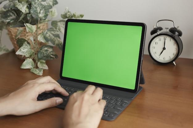 Ręce azjatyckie kobiety za pomocą tabletu mają zielony ekran na biurku