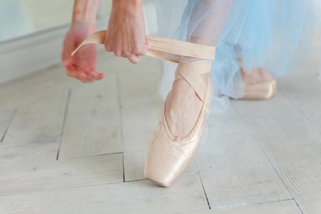 Ręce baleriny kładą buty pointe na nodze w klasie tanecznej