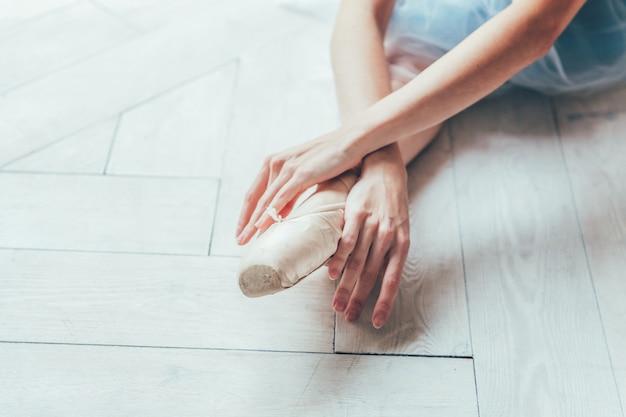 Ręce baleriny w niebieskiej spódniczce tutu zakładają pointe buty na nogawce w białym świetle sali. młoda klasyczna kobieta tancerz baletu w klasie tańca