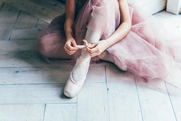 Ręce baleriny w różowej spódniczce tutu zakładają pointe na nogawce w białym świetle