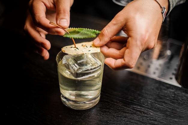 Ręce barmana dekorowanie kieliszka koktajlowego z napojem alkoholowym