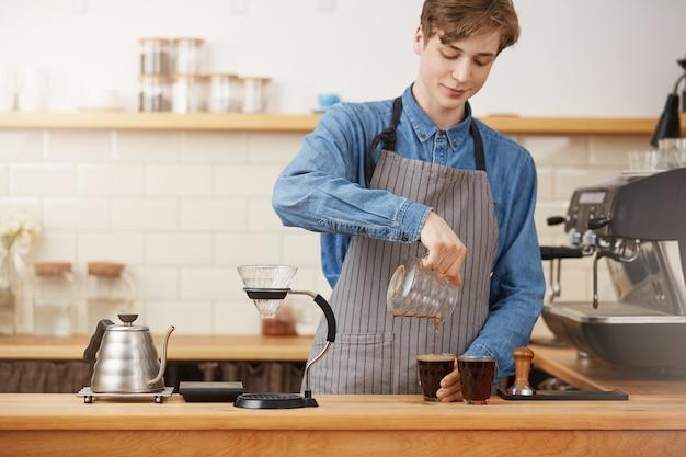 Ręce barmana nalewające alternatywną kawę do dwóch szklanych filiżanek