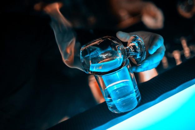 Ręce barmana, szklany kielich na blacie barowym