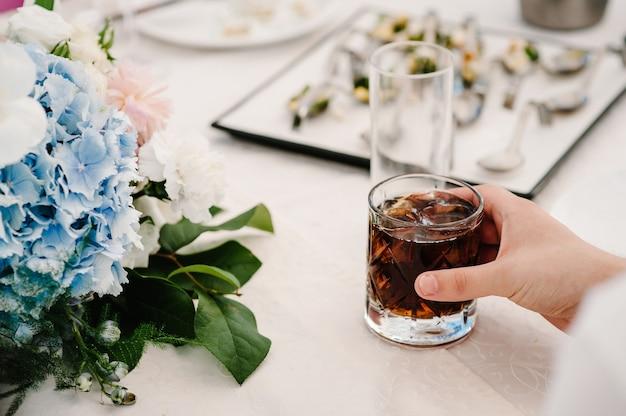 Ręce barmana w barze, restauracji, mężczyzna ze szklaną whisky. kieliszek szkockiej, whisky z kostkami lodu na rustykalnym świątecznym stole, kopia przestrzeń zbliżenie, napoje.