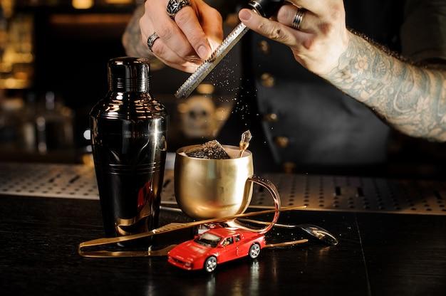 Ręce barmana z tatuażem i pierścieniami wciera gałkę muszkatołową na tarce do miedzianego kubka
