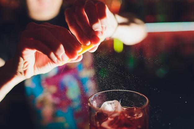 Ręce barmana zraszające sok do kieliszka koktajlowego wypełnionego napojem alkoholowym na ciemnym tle.