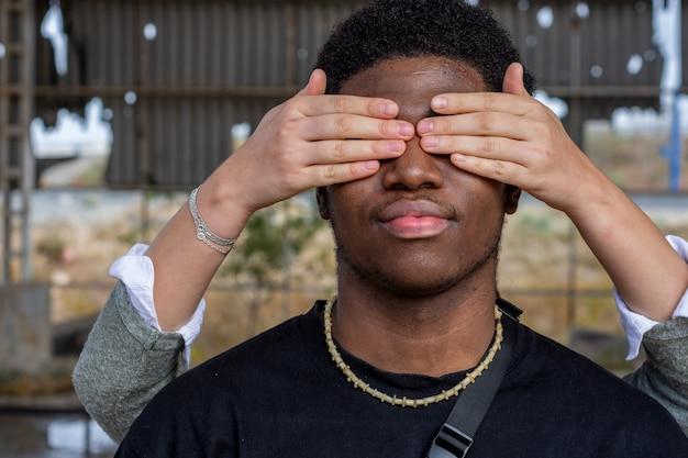Ręce białej kobiety zakrywające oczy czarnego mężczyzny. koncepcja związku. zatrzymać rasizm. tło ściany graffiti.
