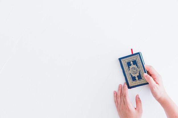 Ręce biorąc książkę koranu