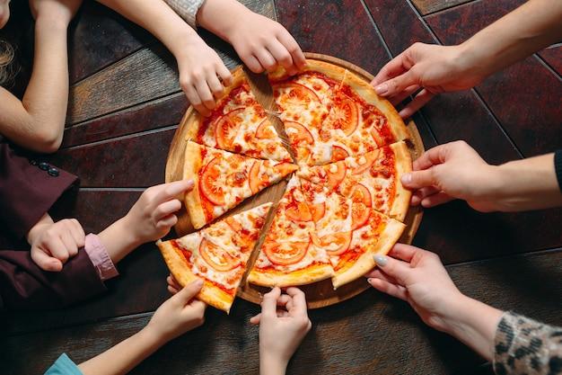 Ręce biorąc plasterki pizzy z drewnianym stole, widok z bliska.