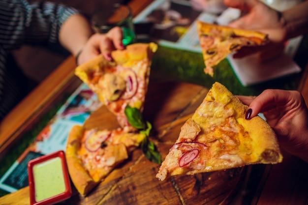 Ręce biorąc plastry pizzy z drewnianej tablicy