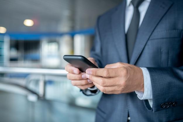 Ręce biznesmena trzymającego smartfona
