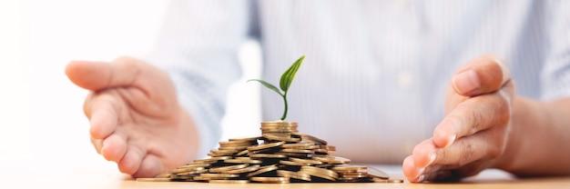 Ręce biznesmena wkładającego monety do kiełkującej rośliny, która osiąga zyski, demonstrując wzrost finansowy poprzez plany oszczędnościowe i programy inwestycyjne.