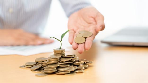 Ręce biznesmena wkładanie monet do kiełkującej rośliny dorastającej do zysku