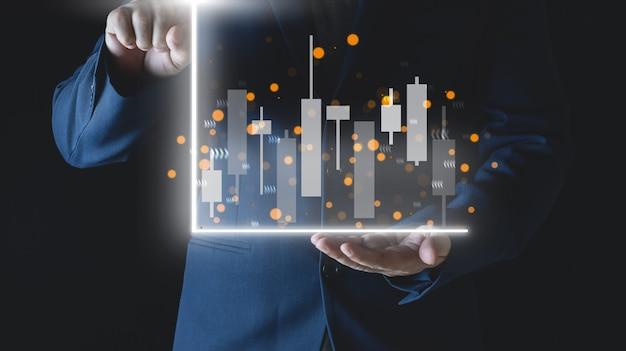 Ręce biznesmena z rynkiem finansów bankingshartstock na wykresie świecowym