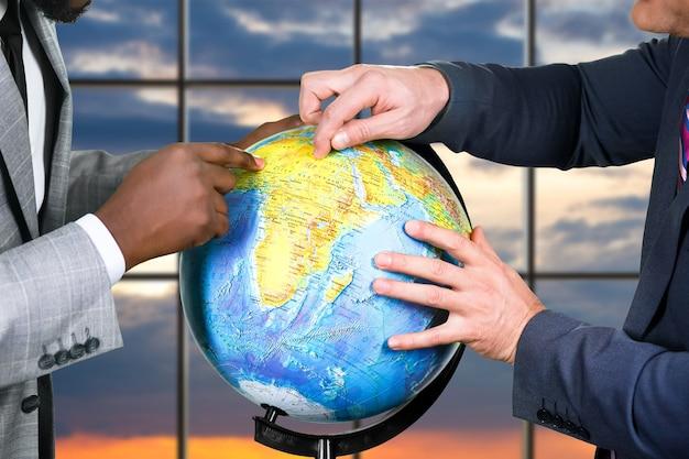 Ręce biznesmenów dotykają kuli ziemskiej. globus na tle wschodu słońca. naukowcy próbują dojść do porozumienia. biznesmeni dzielący świat.