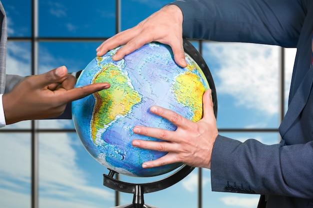 Ręce biznesmenów dotykające kuli ziemskiej. globus na tle zachmurzonego nieba. ważna chwila dla wszystkich. wiedza to potęga.