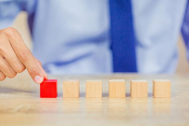 Ręce biznesmenów, układanie drewnianych klocków w kroki.