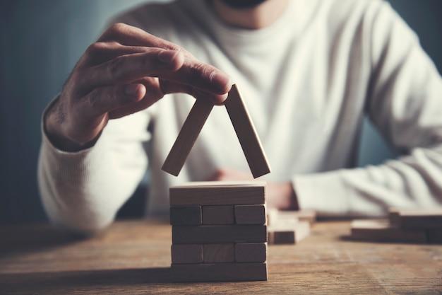 Ręce budują dom z kostek