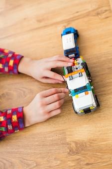 Ręce chłopca poruszają się zabawkową ciężarówką. dziecko bawiące się pojazdem zabawka. technicy muszą się spieszyć. siła wyobraźni.