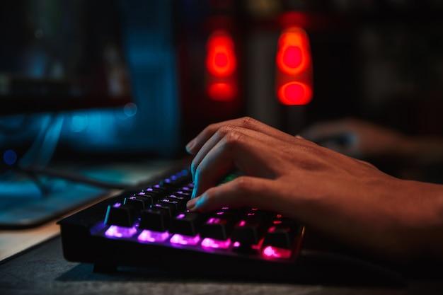 Ręce chłopca profesjonalnych graczy, grając w gry wideo na komputerze w ciemnym pokoju, przy użyciu podświetlanej klawiatury kolorowej
