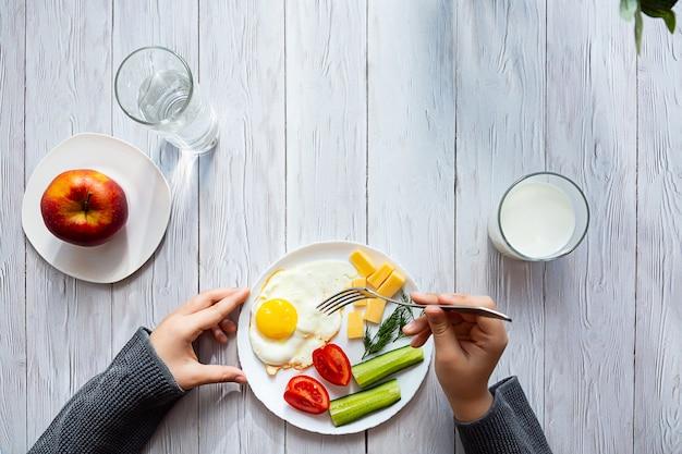 Ręce chłopca trzymają widelec nad talerzem z jajkami sadzonymi.