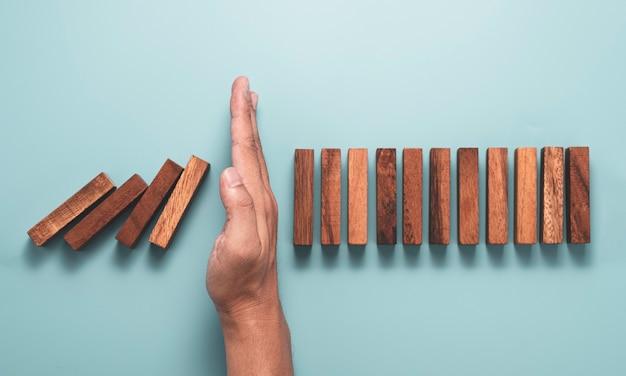 Ręce chronią, aby zatrzymać domina z prostokąta blokowego, a inne stojące.