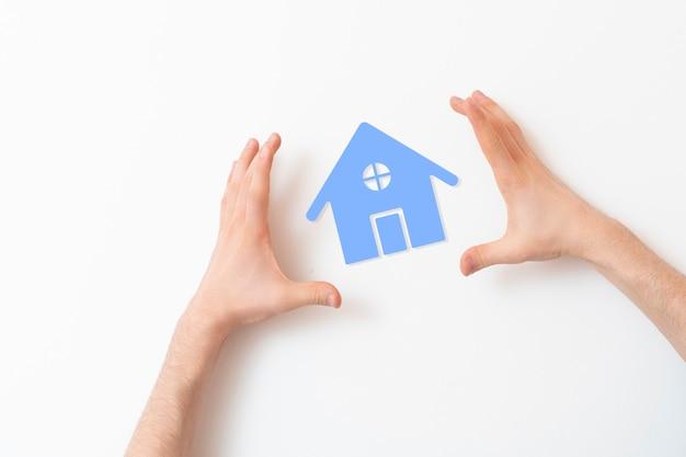 Ręce chronią ikonę domu, koncepcja bezpieczeństwa nieruchomości