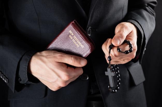 Ręce chrześcijańskiego kapłana ubranego na czarno, trzymającego krucyfiks i książkę nowego testamentu. osoba religijna z biblią i koralikami modlitewnymi, niski obraz.