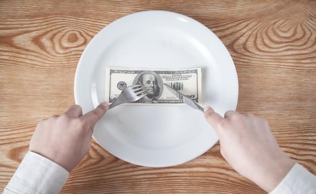 Ręce cięcia banknotu dolara na talerzu.