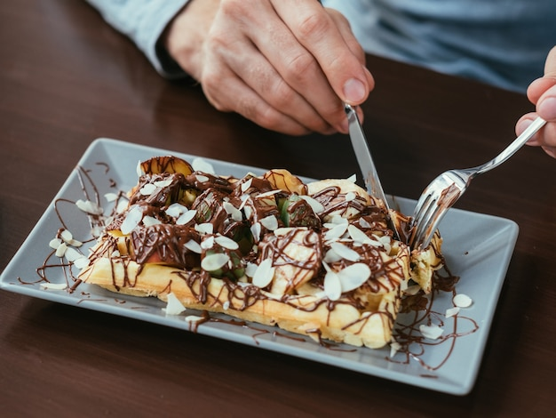 Ręce człowieka cięcia belgijskiego gofra. jedzenie i słodki przysmak