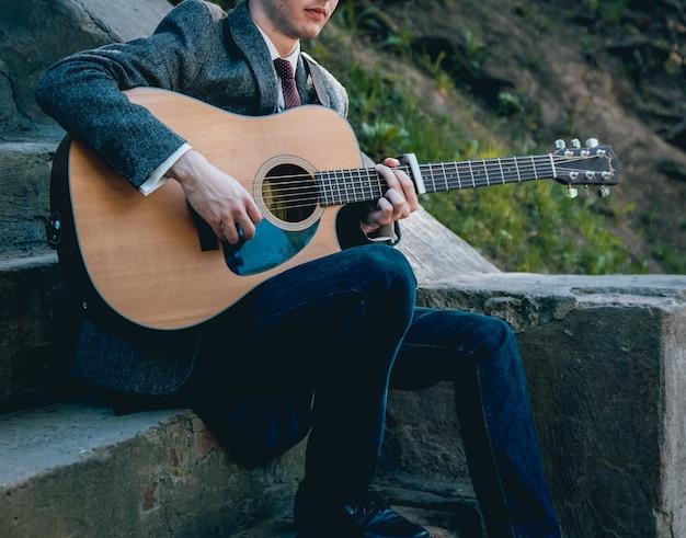 Ręce człowieka, gra na gitarze akustycznej. autentyczne tło.