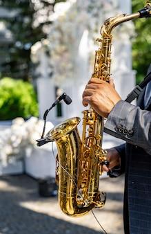 Ręce człowieka grającego na saksofonie. zbliżenie na ręce męskiego saksofonisty grającego na saksofonie tenorowym. muzyka jazzowa, klasyczna i bluesowa na weselu.