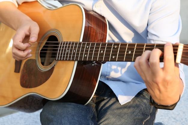 Ręce człowieka, który gra na gitarze akustycznej