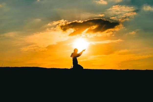 Ręce człowieka modlące się o błogosławieństwo od boga na tle zachodu słońca