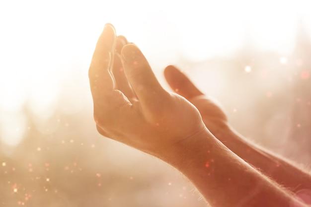 Ręce człowieka modlącego się na krzyżowym tle bokeh