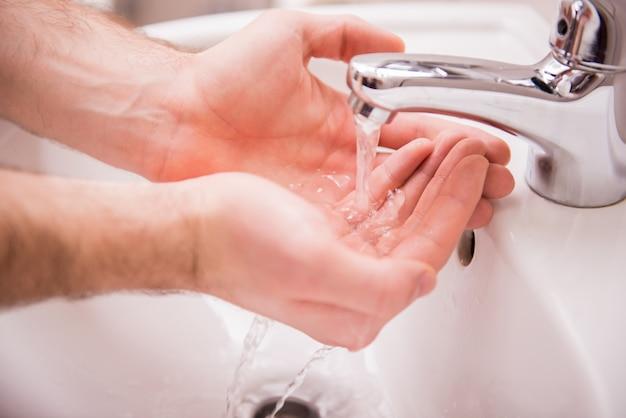 Ręce człowieka myją ręce pod wodą.