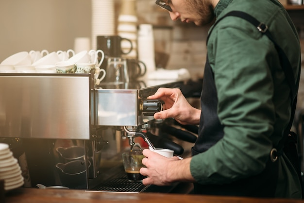 Ręce człowieka nalewa napój z ekspresu do kawy.