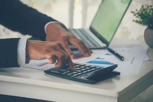 Ręce człowieka obliczanie danych liczbowych wykresu wykresu audytu planowania rachunkowości na raport biznesowy