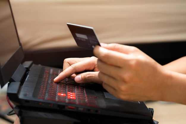 Ręce człowieka przy użyciu komputera przenośnego i posiadania karty kredytowej. koncepcja zakupów online i płatności online.