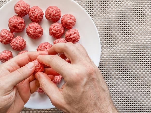 Ręce człowieka przygotowywanie klopsików z surowego mięsa mielonego. domowe gotowanie
