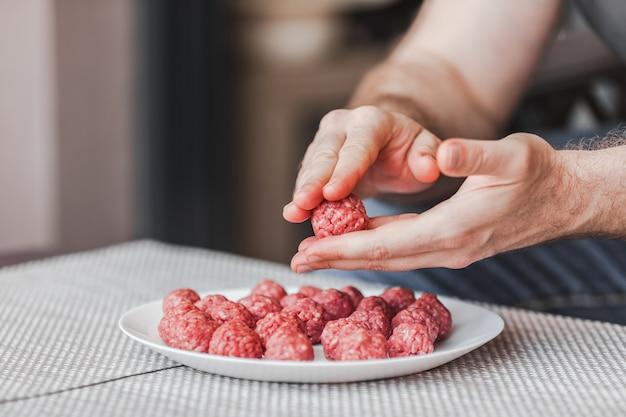 Ręce człowieka przygotowywanie klopsików z surowego mięsa mielonego. styl życia z bliska kompozycja z naturalnym światłem. domowe gotowanie podczas blokady, koncepcja wspólnego sprzątania w domu. widok z boku z miejscem na kopię