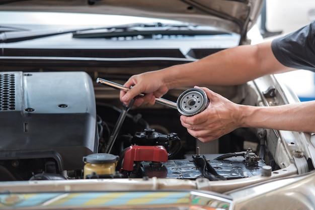 Ręce człowieka, trzymając klucz nasadki filtra oleju i filtr oleju samochodowego przygotowuje się do zmiany.