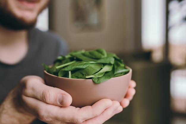 Ręce człowieka, trzymając świeże sałatki zielone liście szpinaku. koncepcja zdrowego wegetariańskiego jedzenia. zielone liście szpinaku. dary natury. błogosławione żniwa.